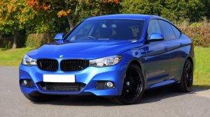 A blue BMW sedan near grass